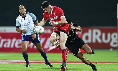 Wales' Joe Goodchild drives through the New Zealand defence on day one of the Emirates Airline Dubai Rugby Sevens