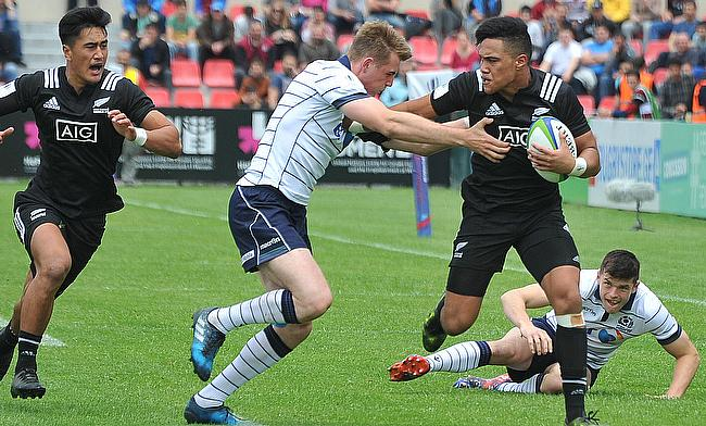 New Zealand winger Tima Faingaanuku hands off a Scotland player on his way to scoring in their Pool B match at AIA Arena